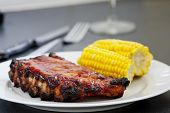 Rack of bbq grilled pork spareribs with corn as a side dish