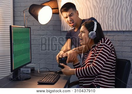 poster of Young couple fighting for joystick while playing video games at home