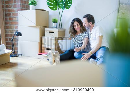 poster of Middle age senior romantic couple in love sitting on the apartment floor with boxes around and using