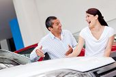 Happy couple looking for a new car at the dealer