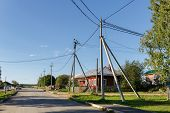 Russian Village In Summer. View Of The Village Street With Traditional Wooden Houses And Old Power L poster