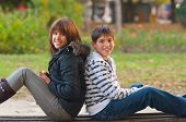Teenage boy and girl spending time together in the park on beautiful autumn day