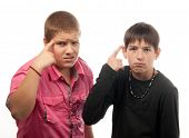 Two serious teenage boys showing on their heads with index finger insinuating stupidity or craziness