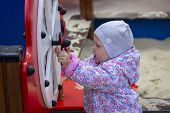 Baby Girl Spinning A Toy Wheel In The Playground. The Girl Plays In The Yard. The Kid In A Gray Hat  poster