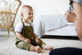 Picture Of Cute Charming European Infant Sitting Barefooted On Carpet At Home, Having Joyful Excited poster