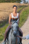 Young attractive girl rides a horse at sunset