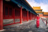 Chinese Lady Walk In Red Cheongsam Dress In Ancient Chinese Forbidden Palace, Beijing City, China, A poster