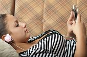 Beautiful teenage girl listens to music on the mobile phone while lying on the couch