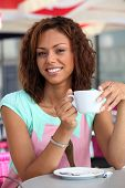 half-breed damsel having coffee outdoors