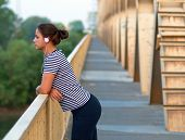 Young attractive girl listening to music while standing on the bridge