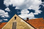 Old Roof On A Blue Cloudy Sky