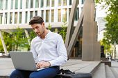 Image of a serious concentrated young businessman sitting outdoors on the street on bench using lapt poster