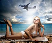 a woman on the beach and a airplane