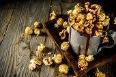 Homemade Sweet Caramel Pop Corn, With Caramel Topping, Dark Rustic Background Copy Space poster