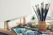Artistic Equipment In Studio: Canvas On Wooden Easel, Paint Brushes, Paints And Used Palette.  Copy  poster
