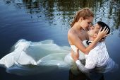 Love and passion - kiss of married young couple in water