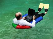 stock photo of flipper  - A businessman working from home dressed in business attire floating in a swimming pool on his laptop and wearing yellow flippers - JPG