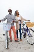 Front view of happy senior African-American couple standing with bicycles on the beach on cloudy day poster