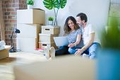 Middle age senior romantic couple in love sitting on the apartment floor with boxes around and using poster