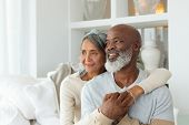 Front view of senior diverse couple sitting on a white couch in beach house. Authentic Senior Retire poster