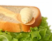 stock photo of margarine  - Butter curl on wooden spoon with bread on background - JPG
