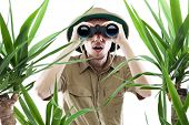 image of jungle birds  - Young man looking through binoculars with an amazed expression palm trees on foreground out of focus isolated on white - JPG