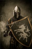 stock photo of sword  - Medieval knight with sword and shield against stone wall - JPG