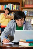 Student - Young Asian man in library with laptop learning, a female student standing in the Backgrou