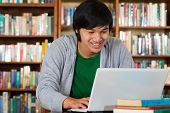 Student - Young Asian man in library with laptop and a pile of books learns