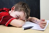 stock photo of dyslexia  - Boy with poor spelling and low self esteem has written on himself - JPG