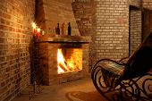 stock photo of cozy hearth  - Rocking chair by the fireplace in brick room and candles - JPG