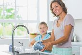 pic of suds  - Happy mother and daughter doing the washing up together in kitchen - JPG