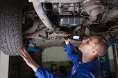 Male mechanic examining car using flashlight