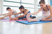Women stretching in yoga class in fitness studio