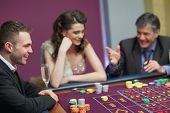 stock photo of crap  - Men and woman talking at craps game in casino - JPG