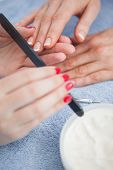 Close-up of woman filing fingernail at nail salon