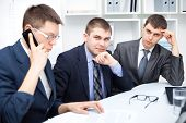 Team junge Geschäftsleute arbeiten zusammen im Büro, einer von ihnen sprechen auf einem Handy