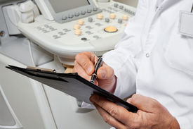 foto of ultrasonic  - Midsection of male doctor writing on clipboard with ultrasonic machine in background - JPG