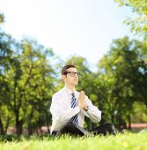 Young businessman doing yoga exercise seated on a green grass in a park, shot with a tilt and shift lens