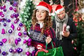 Portrait of beautiful young woman carrying shopping bag at Christmas store with man in background