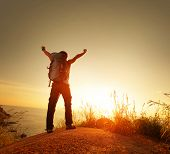Hiker with backpack and raised hands enjoying sunset over sea