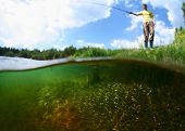 Young man fishing in a pond in a sunny day. Focus on the weed underwater