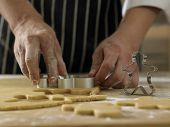 chef cutting the ginger breadman from the dough