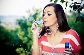 Cute young woman blowing soap bubbles, with blurred background