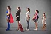 stock photo of trolley  - evolution of woman from small child to super hero - JPG