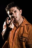 stock photo of obscene  - Angry Young Man in Prison acting obscene - JPG