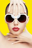 closeup portrait of young gorgeous caucasian woman wearing sunglasses, over yellow background