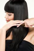 close-up beauty portrait of young caucasian brunette brushing her hair