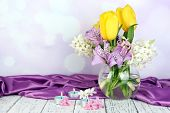Flowers in vase with candles on table on bright background