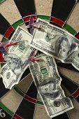Dartboard with darts and hundred dollar bills